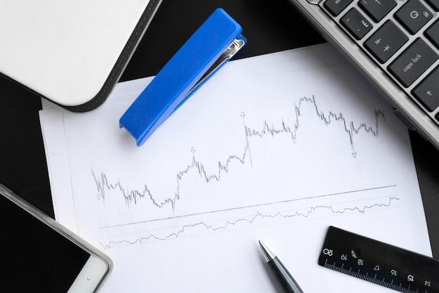 Zakelijke werkplek met toetsenbord en papieren met grafieken