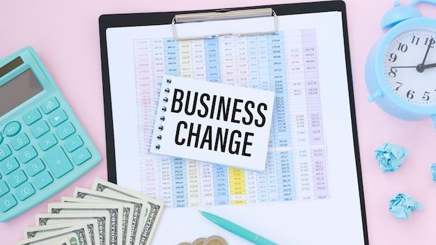 Zakelijke wijzigingstekst op notitieboekje met potlood, rekenmachine, geld en armklok