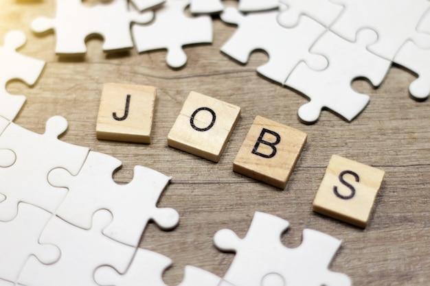 Zakelijke woorden jobs in kruiswoordraadsel met houten kubussen en puzzel.