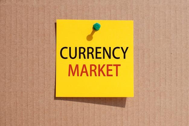 Zakelijke zin - valutamarkt - geschreven op geel vierkant papier en vastgemaakt op karton, concept