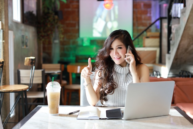 Zaken die online, jonge aziatische vrouw in toevallige kleding die aan computer werken verkopen