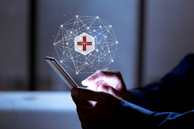 Zaken die telefoon, met medisch pictogram, verzekerings online en medisch online concept gebruiken.