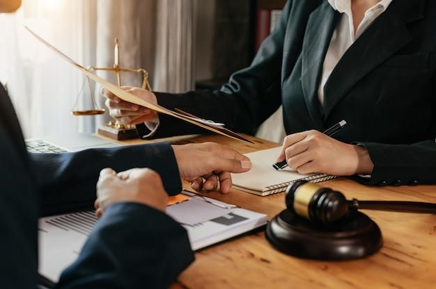 Zaken en advocaten bespreken contractpapieren met koperen schaal op bureau in kantoor. wet, juridische dienstverlening, advies, justitie en recht concept.