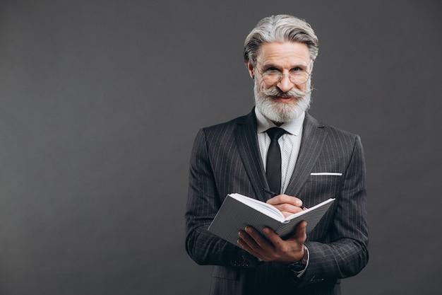 Zaken en modieuze bebaarde volwassen man in een grijs pak schrijven in zijn notitieblok kopie ruimte op de grijze muur.
