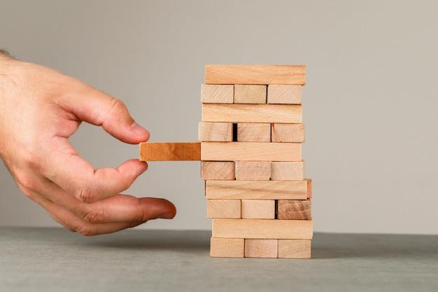 Zaken en risico en beheerconcept op grijs en wit muur zijaanzicht. hand terugtrekken houten blok.