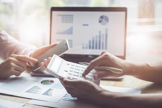 Zaken en vennootschap die gebruikend calculator bespreken om balans jaarlijks met holdingspen te herzien en laptop computer te gebruiken om begroting te berekenen. auditintegriteit voor investeringsconcept.