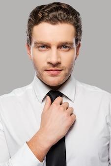 Zaken er goed uit laten zien. zelfverzekerde jonge man in overhemd en stropdas die zijn stropdas aanpast en naar de camera kijkt terwijl hij tegen een grijze achtergrond staat