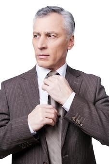 Zaken er goed uit laten zien. zelfverzekerde volwassen man in formalwear die zijn stropdas aanpast en wegkijkt terwijl hij tegen een witte achtergrond staat