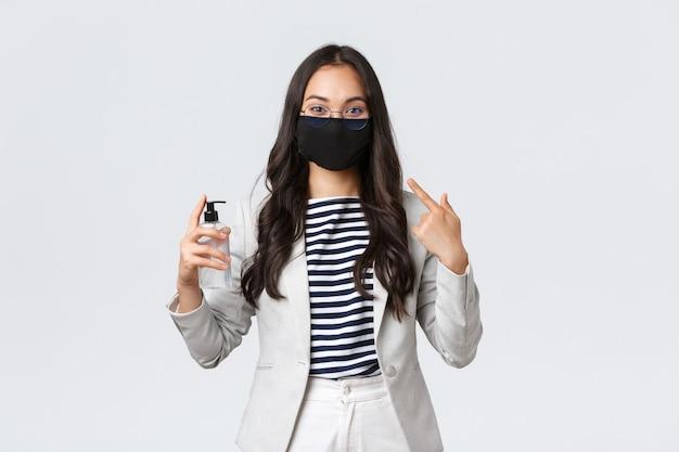 Zaken, financiën en werkgelegenheid, covid-19 preventie van virus en social distancing concept. leuke aziatische kantoordame legt het belang uit van het dragen van gezichtsmaskers en het gebruik van handdesinfecterende middelen tijdens pandemie
