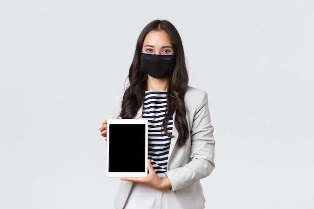 Zaken, financiën en werkgelegenheid, covid-19 preventie van virus en social distancing concept. zelfverzekerde vrouwelijke makelaar in onroerend goed die deal voor klant op digitaal tabletscherm toont, gezichtsmasker draagt