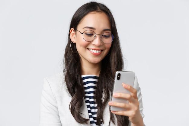 Zaken, financiën en werkgelegenheid, vrouwelijk succesvol ondernemersconcept. close-up van stijlvolle moderne zakenvrouw in pak en bril messaging, met behulp van mobiele telefoon