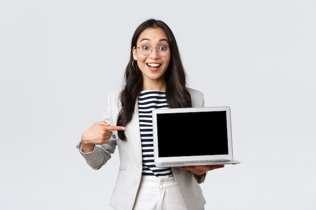 Zaken, financiën en werkgelegenheid, vrouwelijk succesvol ondernemersconcept. enthousiaste officemanager die haar presentatie op laptop toont, naar het scherm wijst en geamuseerd glimlacht. Gratis Foto