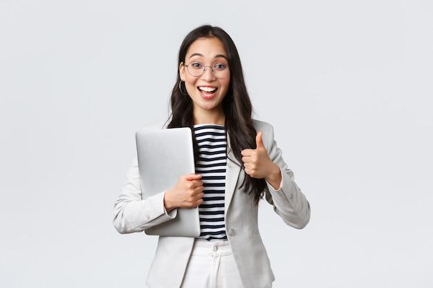 Zaken, financiën en werkgelegenheid, vrouwelijk succesvol ondernemersconcept. jonge zelfverzekerde zakenvrouw met een bril, met een duim omhoog gebaar, houd de laptop vast, garandeer de beste servicekwaliteit