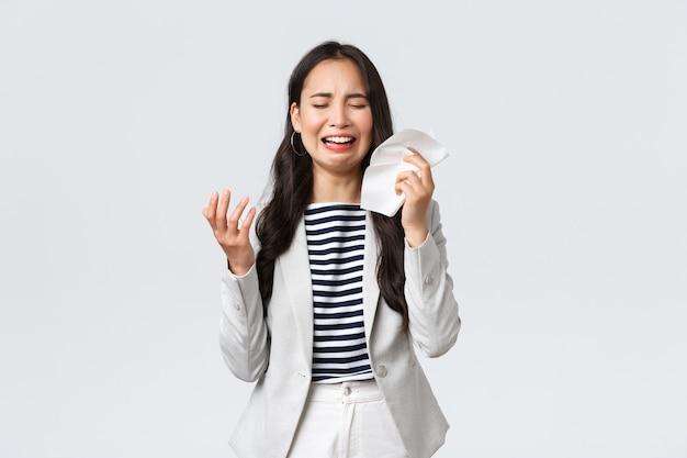 Zaken, financiën en werkgelegenheid, vrouwelijk succesvol ondernemersconcept. ongemakkelijke verontruste aziatische kantoordame die zich verdrietig voelt, huilt en snikt, tranen afveegt met tissues, klaagt