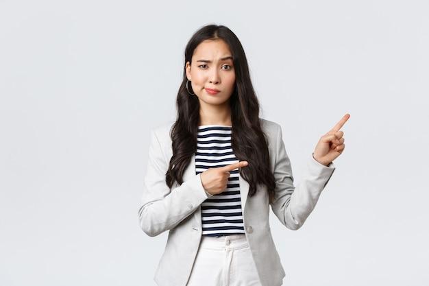 Zaken, financiën en werkgelegenheid, vrouwelijk succesvol ondernemersconcept. sceptische en aarzelende jonge aziatische zakenvrouw vertrouw deze promo niet, grijns twijfelachtig en wijzend naar de rechterbovenhoek