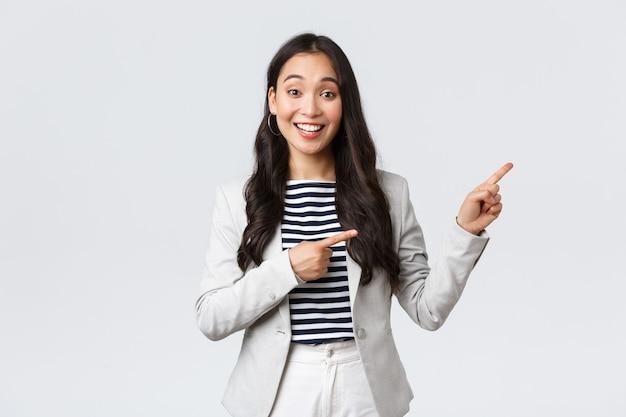Zaken, financiën en werkgelegenheid, vrouwelijk succesvol ondernemersconcept. vriendelijk ogende, schattige vrouwelijke officemanager die graag helpt, wijst naar de rechterbovenhoek, toont de weg en glimlacht