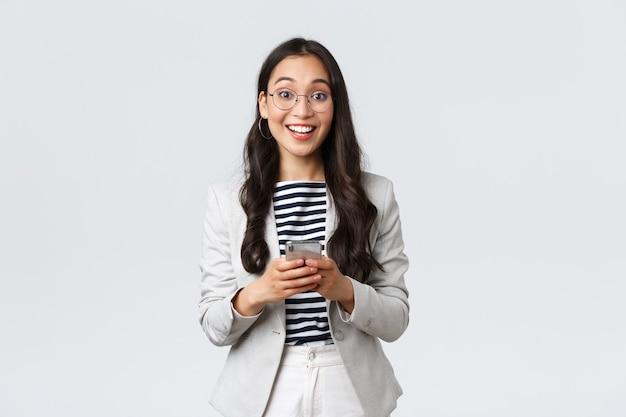 Zaken, financiën en werkgelegenheid, vrouwelijk succesvol ondernemersconcept. vrolijke, gelukkige aziatische zakenvrouw, officemanager die een vrolijke camera kijkt met een glimlach, met behulp van smartphone