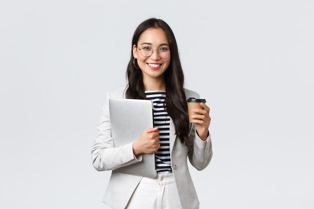 Zaken, financiën en werkgelegenheid, vrouwelijk succesvol ondernemersconcept. zelfverzekerde knappe zakenvrouw in een bril en pak die afhaalkoffie drinkt en een werklaptop draagt