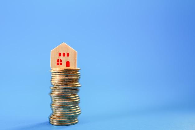 Zaken, hypotheek, hypotheekconcept. close-up van blokhuisblok bovenop stapel gouden muntstukken op blauw met exemplaarruimte.
