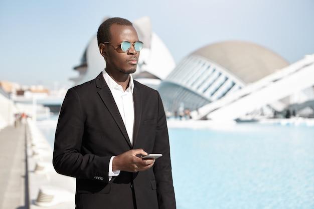 Zaken, levensstijl, succes, carrière en mensen. openluchtportret van elegante modieuze zwarte financier in formeel kostuum en zonnebril die mobiele telefoon met behulp van
