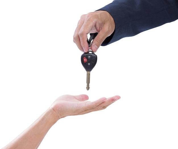 Zaken man overhandigen auto sleutels op afstand geven aan een casual senior man, geïsoleerd op wit