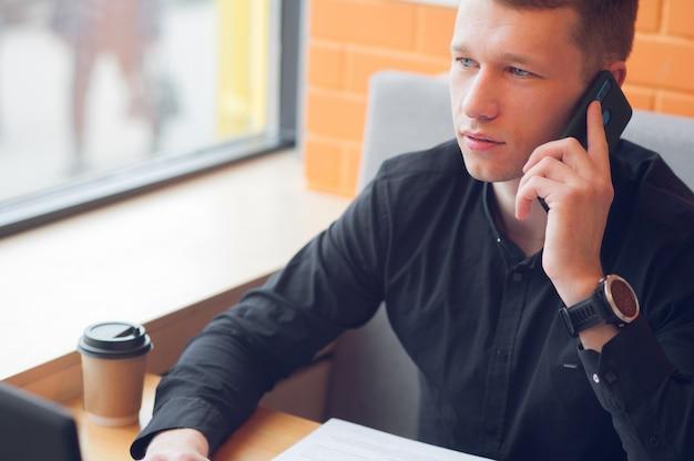 Zaken van een kopje koffie en geniet van je werk in een coffeeshop terwijl je aan de telefoon praat
