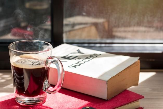 Zaken van succesboek en zwarte koffie op hout dichtbij venster in lichte ochtend