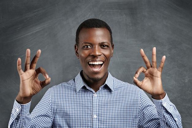Zaken, vervoerder en succes. jonge donkere zakenman die gelukkige blik heeft, glimlachend, zijn mond wijd open houdt, gebarend, ok teken na het sluiten van winstgevende overeenkomst. lichaamstaal