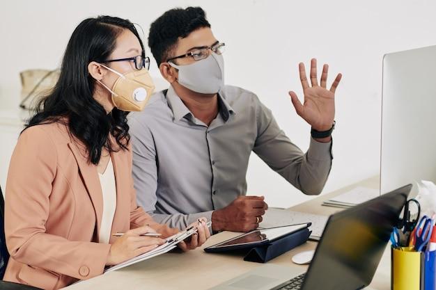Zakencollega's in beschermende maskers die online conferentie hebben met collega's uit andere landen