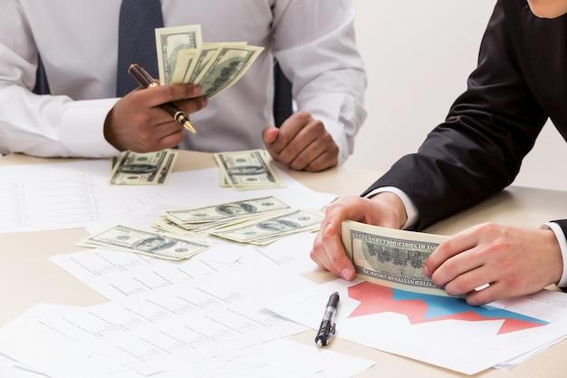 Zakenlieden delen winst succesvolle jongens tellen geld zakelijk succes