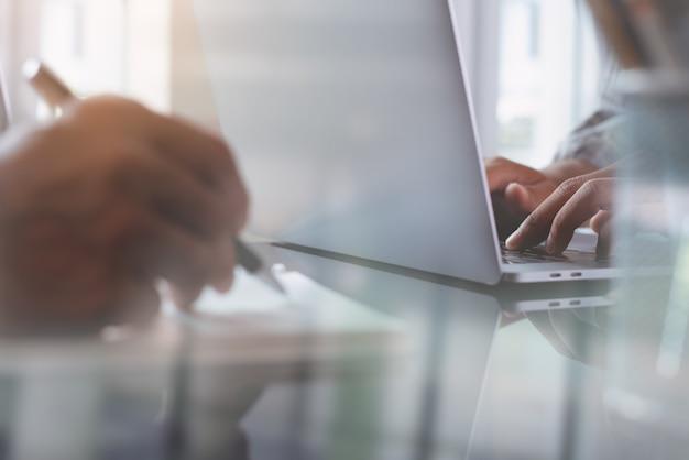 Zakenlieden die aan laptop computer in modern bureau werken