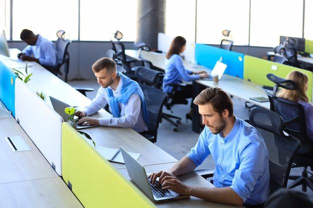 Zakenlieden die beursgegevens analyseren terwijl ze op kantoor werken.
