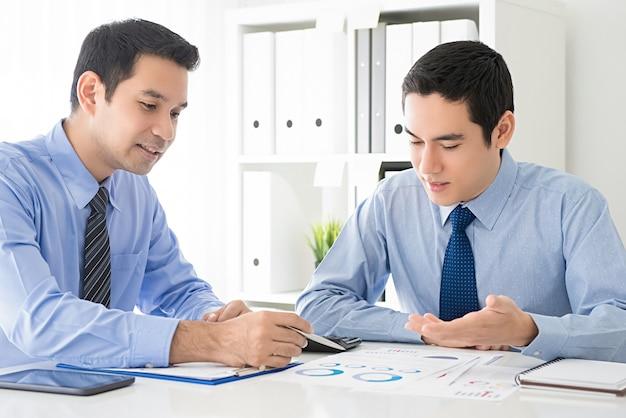 Zakenlieden die de documenten van de het werkpresentatie in het bureau bespreken