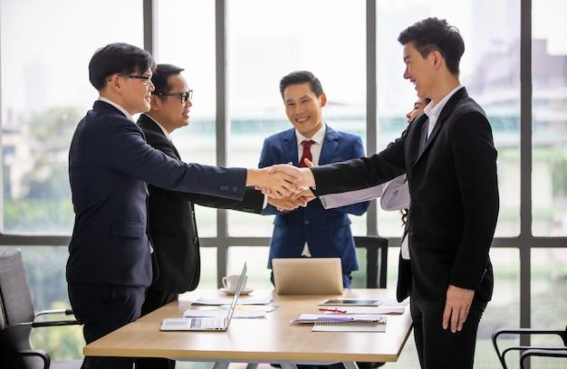 Zakenlieden die elkaar de hand schudden tijdens een bijeenkomst op kantoor