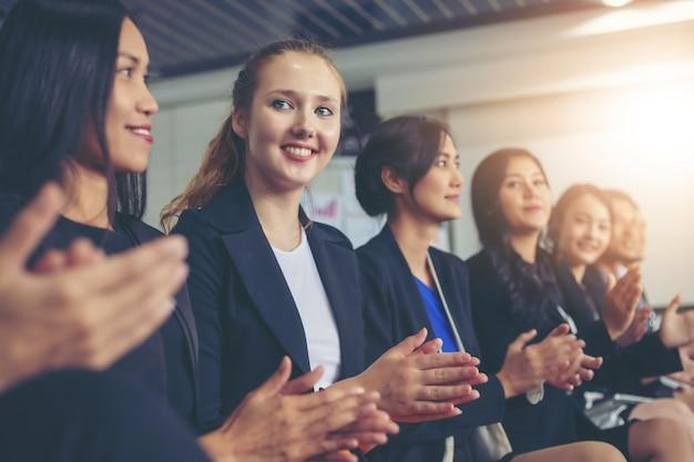 Zakenlieden die in een commerciële vergadering toejuichen