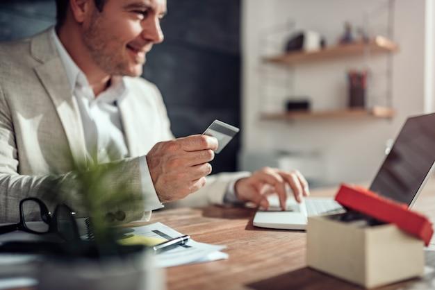 Zakenlieden die laptop met behulp van en online met creditcard betalen