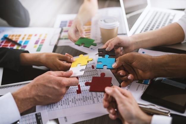 Zakenlieden die samenwerken om een gekleurde puzzel te bouwen