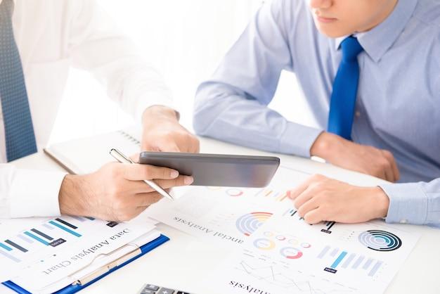 Zakenlieden die tabletcomputer met behulp van die financiële gegevens bespreken