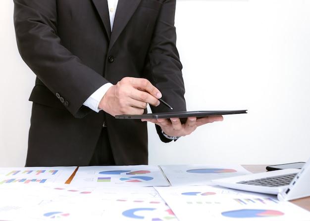 Zakenlieden die tabletten houden, die grafieken op bureaus analyseren