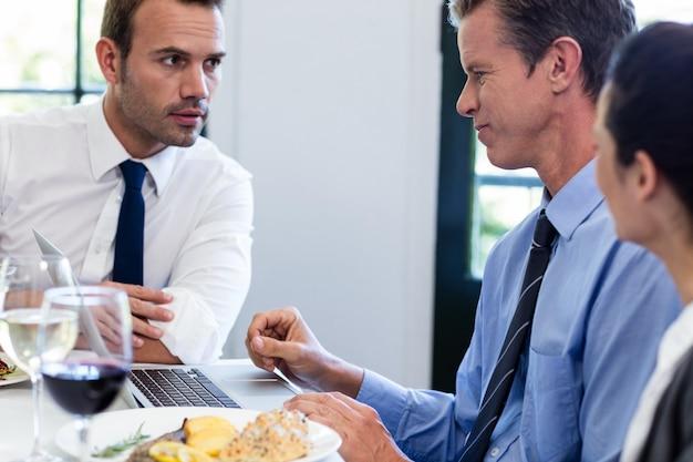 Zakenlieden die tijdens een bedrijfslunchvergadering bespreken