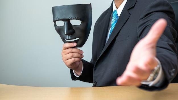 Zakenlieden die zwart masker en handdruk elkaar houden bij bureau