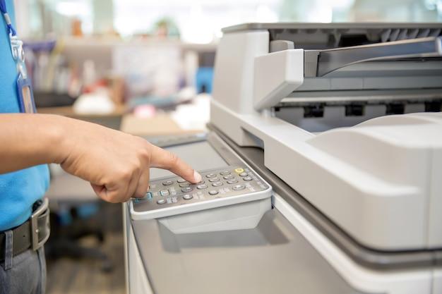 Zakenlieden drukken op de knop op het paneel van fotokopieerapparaat