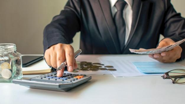 Zakenlieden drukken op een rekenmachine om rekeningen en inkomen te verifiëren, zaken die verband houden met financieel en investeringsbeheer, zachte focus.