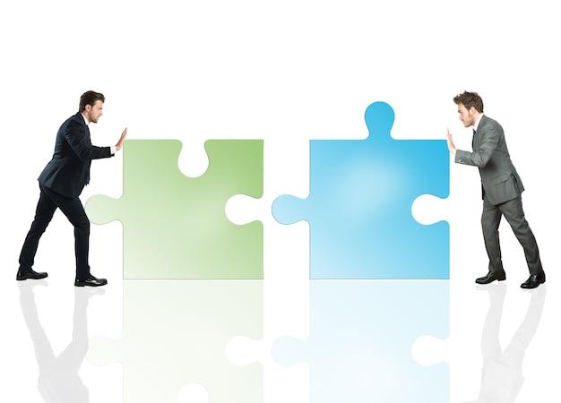 Zakenlieden duwen een puzzelstukjes in elkaar