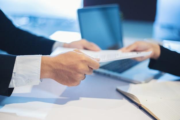 Zakenlieden en onderneemsters die documenten bespreken voor het concept van het baangesprek