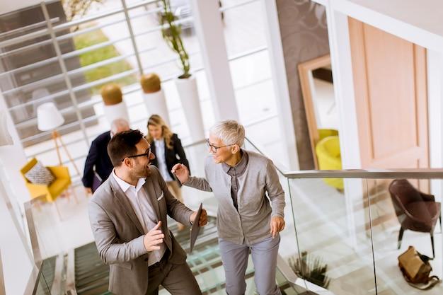 Zakenlieden en onderneemsters die en treden in een bureaugebouw lopen nemen