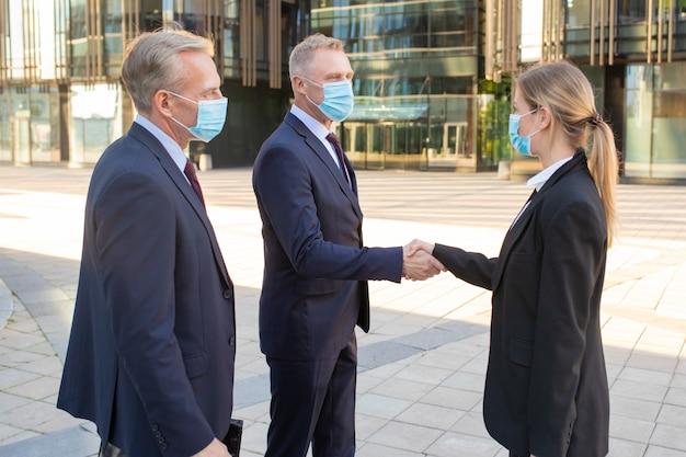Zakenlieden en vrouw in gezichtsmaskers en kantoorpakken bijeen in de stad, handen schudden in de buurt van gebouw. zijaanzicht geschoten. communicatie- en virusbeschermingsconcept