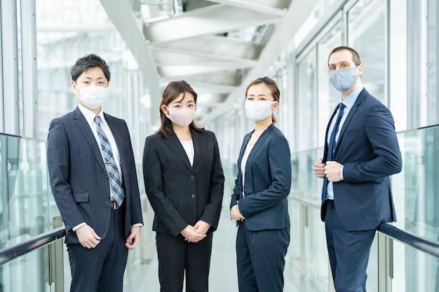 Zakenlieden en -vrouwen die een masker en pakken dragen