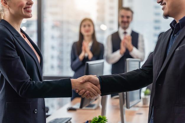 Zakenlieden en zakenvrouw handen schudden tijdens een bijeenkomst met bereiken een overeenkomst voor het bedrijfsleven