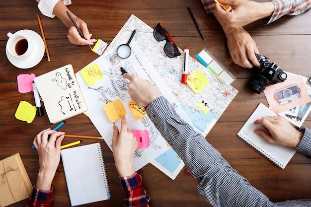 Zakenlieden handen op houten tafel met documenten en ontwerpen